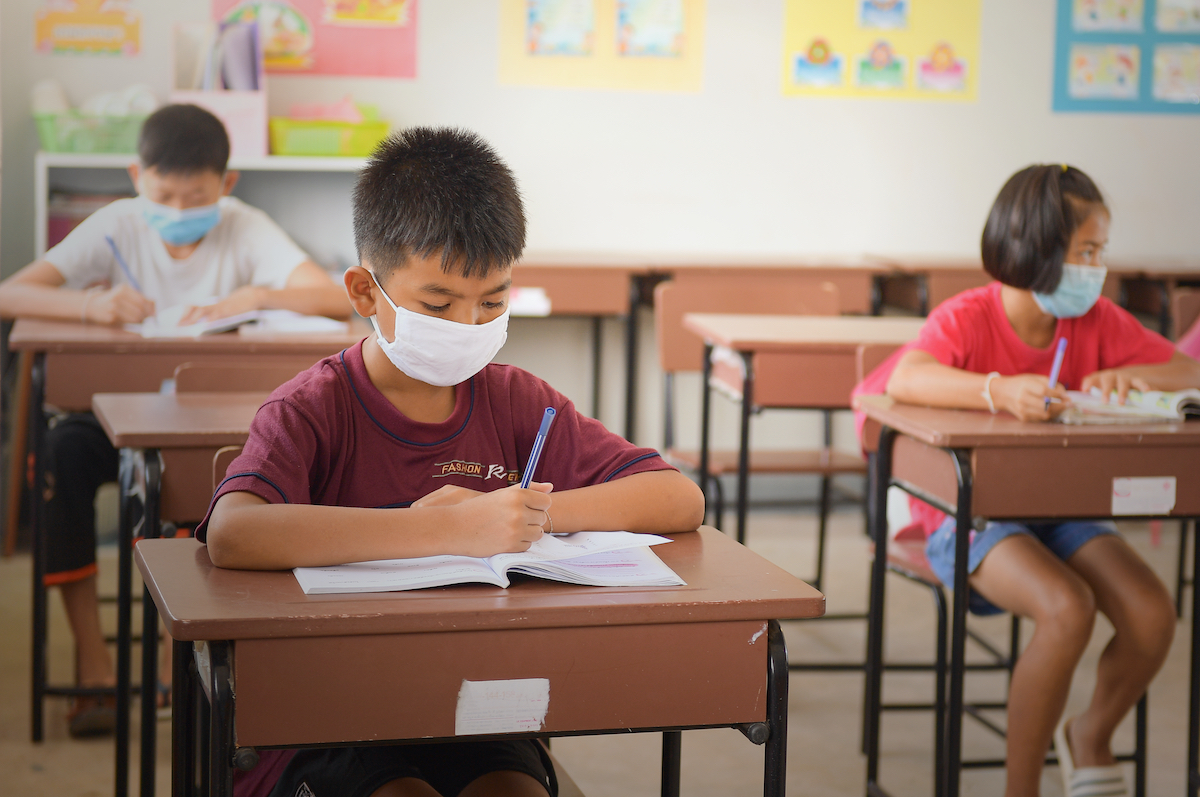 a young asian boy with a face mask writes in a notebook in a classroom. two other students are in the class seated several desks away