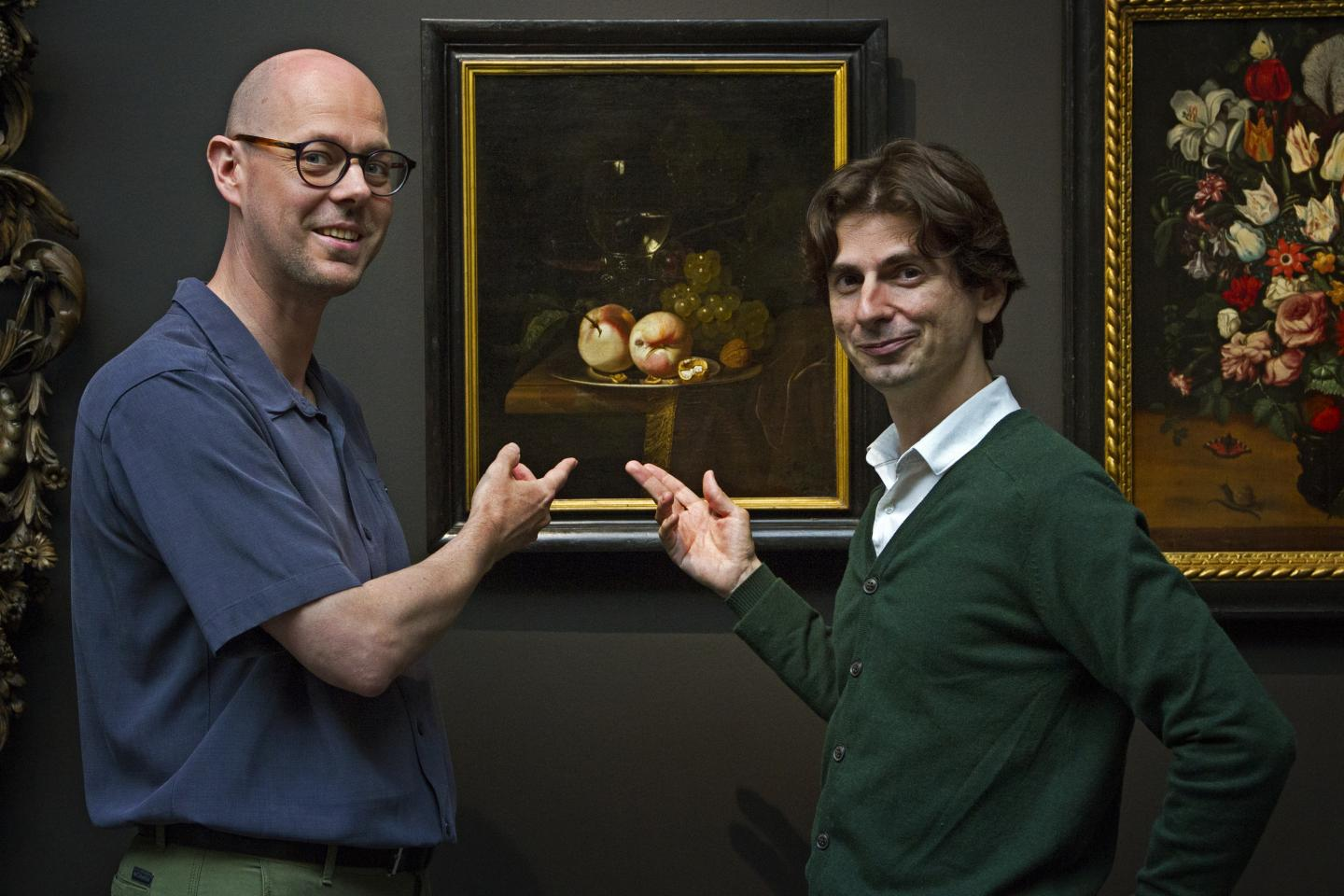 two men standing in front of oil painting in museum