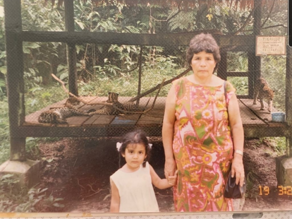 an old photo of a grandmother and her grand daughter holding hands in front of a zoo cage of tigers