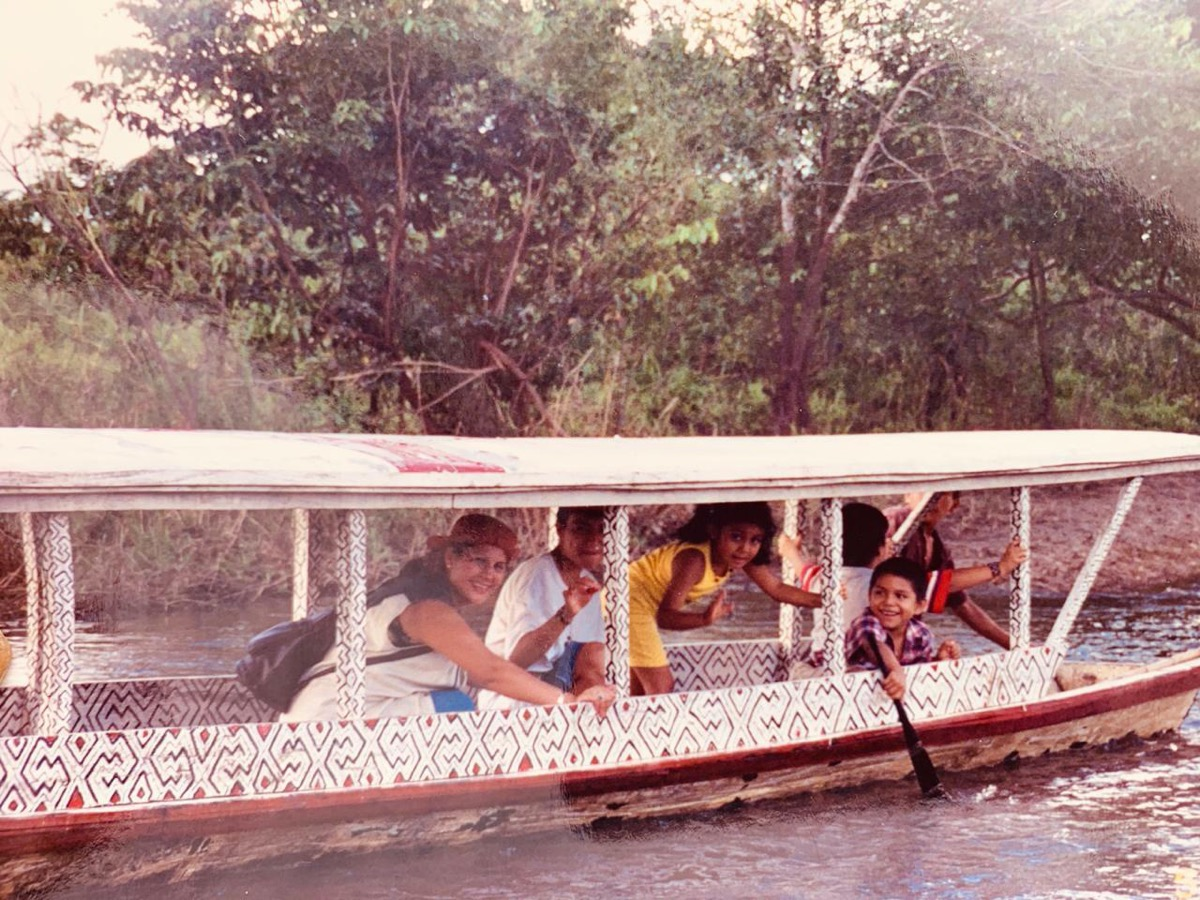 an old photo of a family rowing on a boat in the amazon jungle