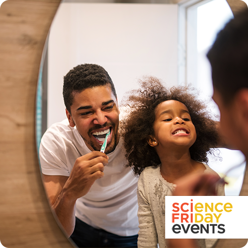 a father and 5-year-old daughter looking into a mirror; the father is brushing his teeth and smiling, and the daughter is smiling large