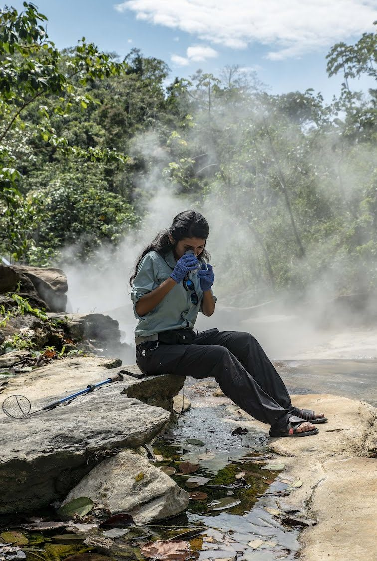 a woman scientist wearing gloves looks a specimen through a microscope as she sits on rocks along a steaming river