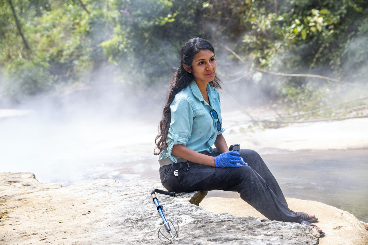 a woman scientist sitting on a rock next to a steamy river holding a sample of microbes