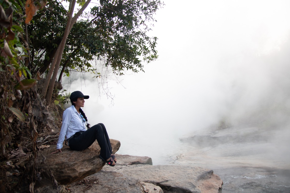 a woman in hat sits next to a river, there is so much steam coming off the river it looks like she is sitting in a cloud