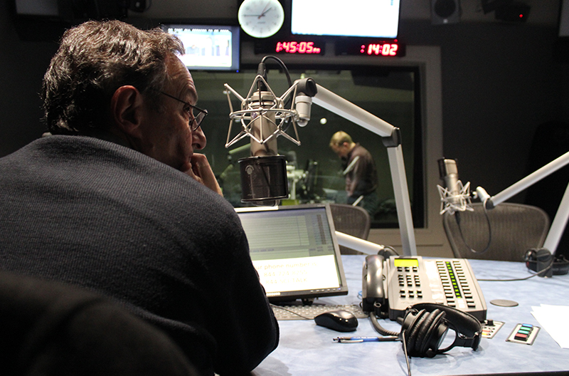 Ira Flatow in profile sitting in a radio studio, shot from behind as he looks to his right, with a microphone, phone and computer set up in front of him