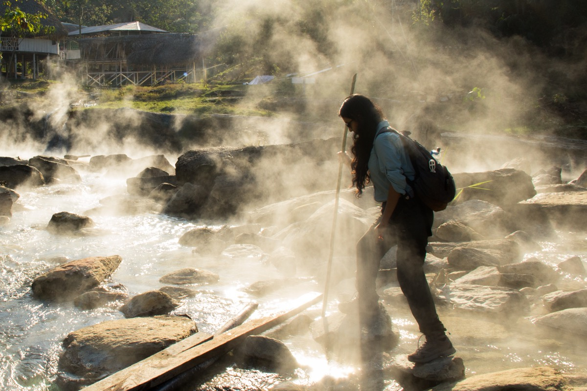 a woman scientist walks across river rocks with steam surrounding her