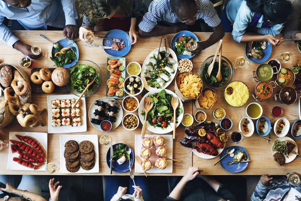 aerial view of a table full of food and drinks with various arms reaching out to eat