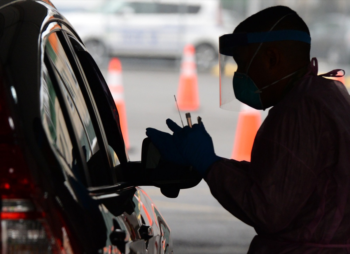 a medic holding a swab and test tube next to a car in the shadows