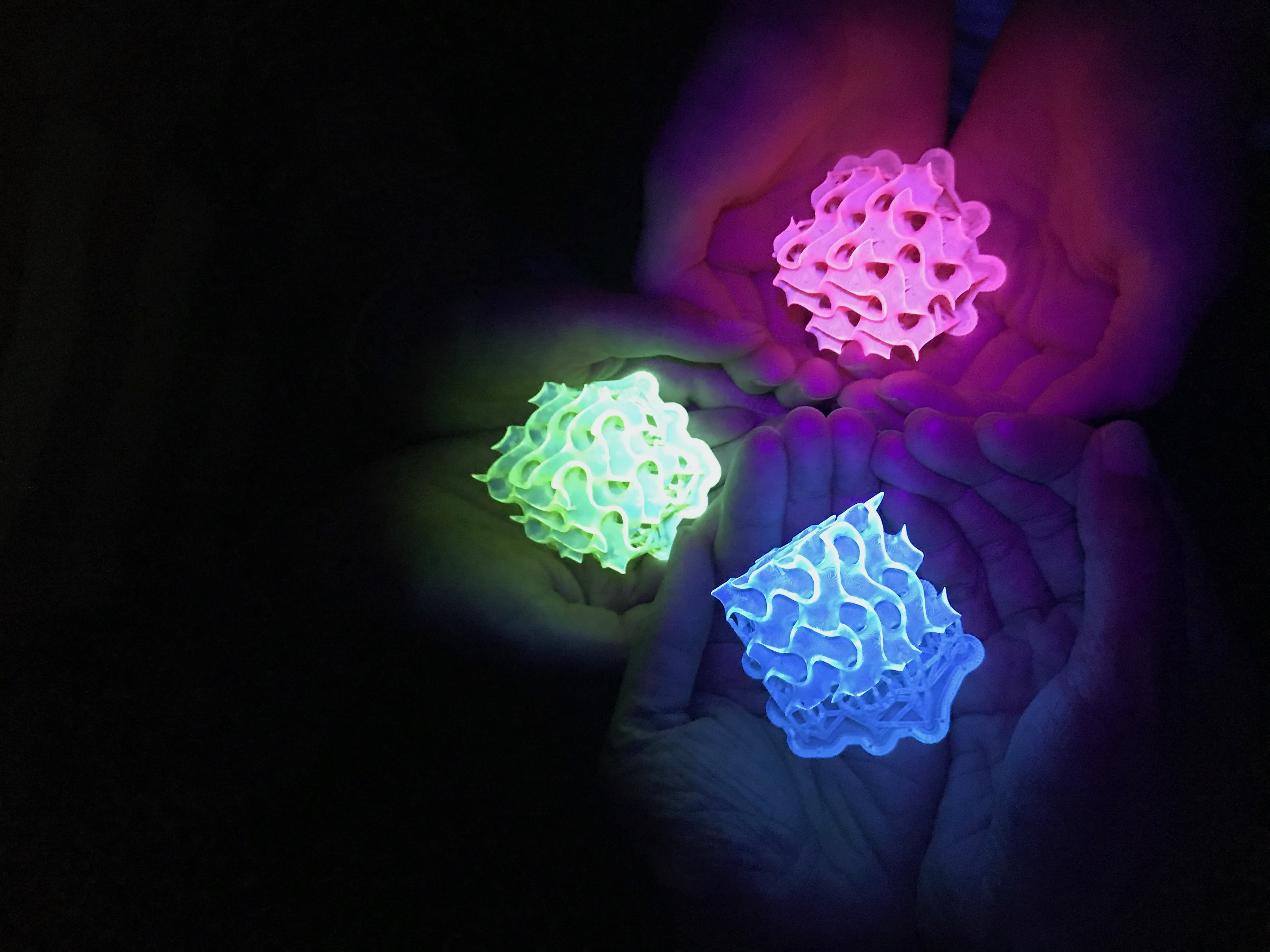 three pairs of hands holding Glowing 3D-printed gyroids