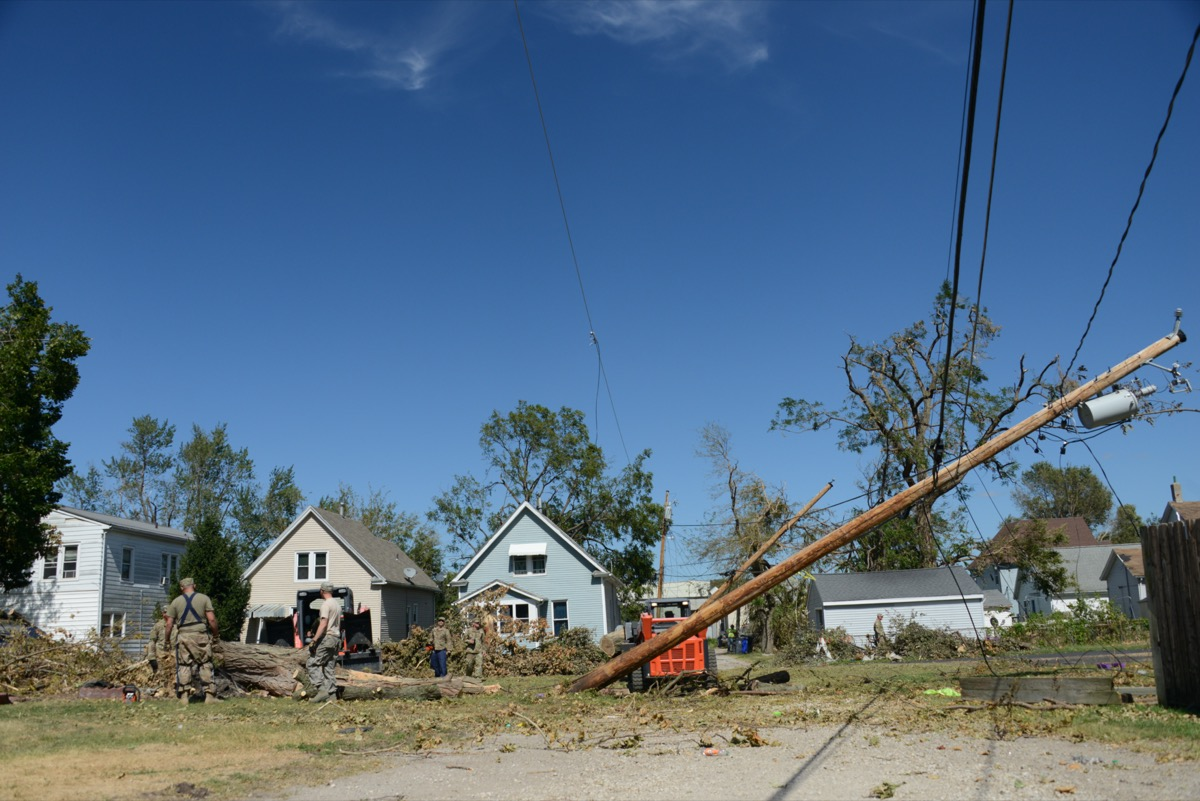 a bunch of downed trees and power lines in front of a row of houses.