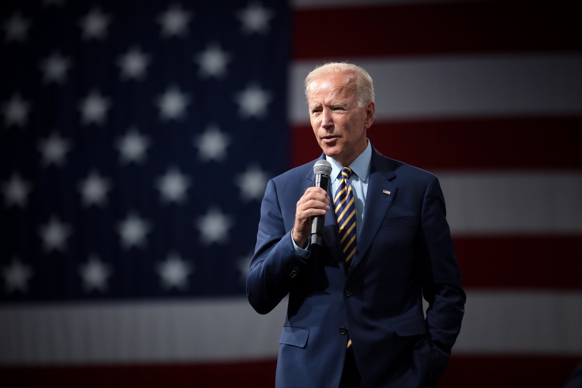 a man in a suit speaking into a microphone, standing in front of an american flag