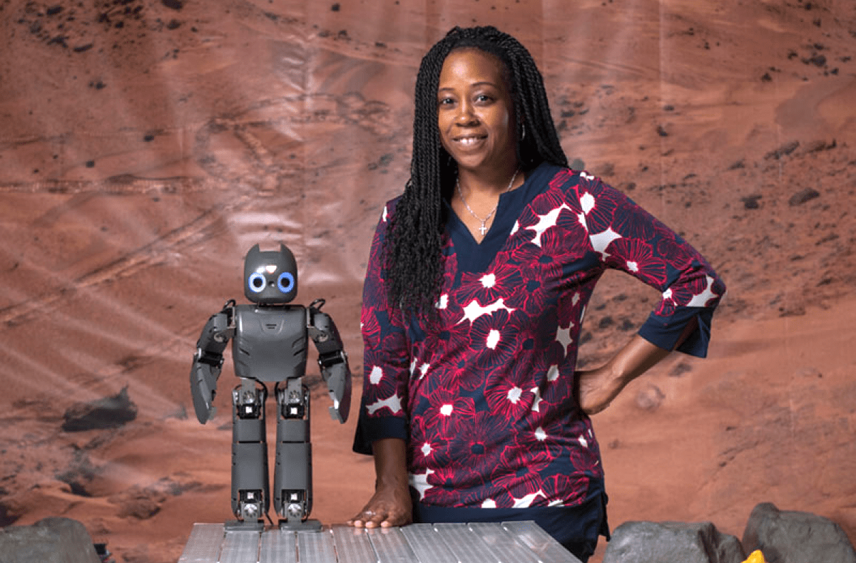 a black woman standing next to a small humanoid robot