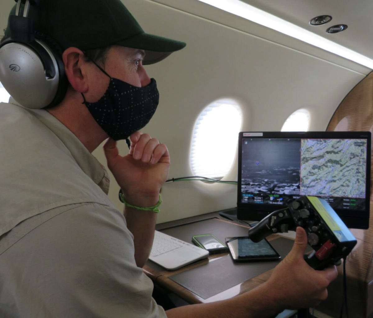 a man wearing a face mask holds a video game-like remote control and looks at a computer screen of maps. he's inside of a plane cabin