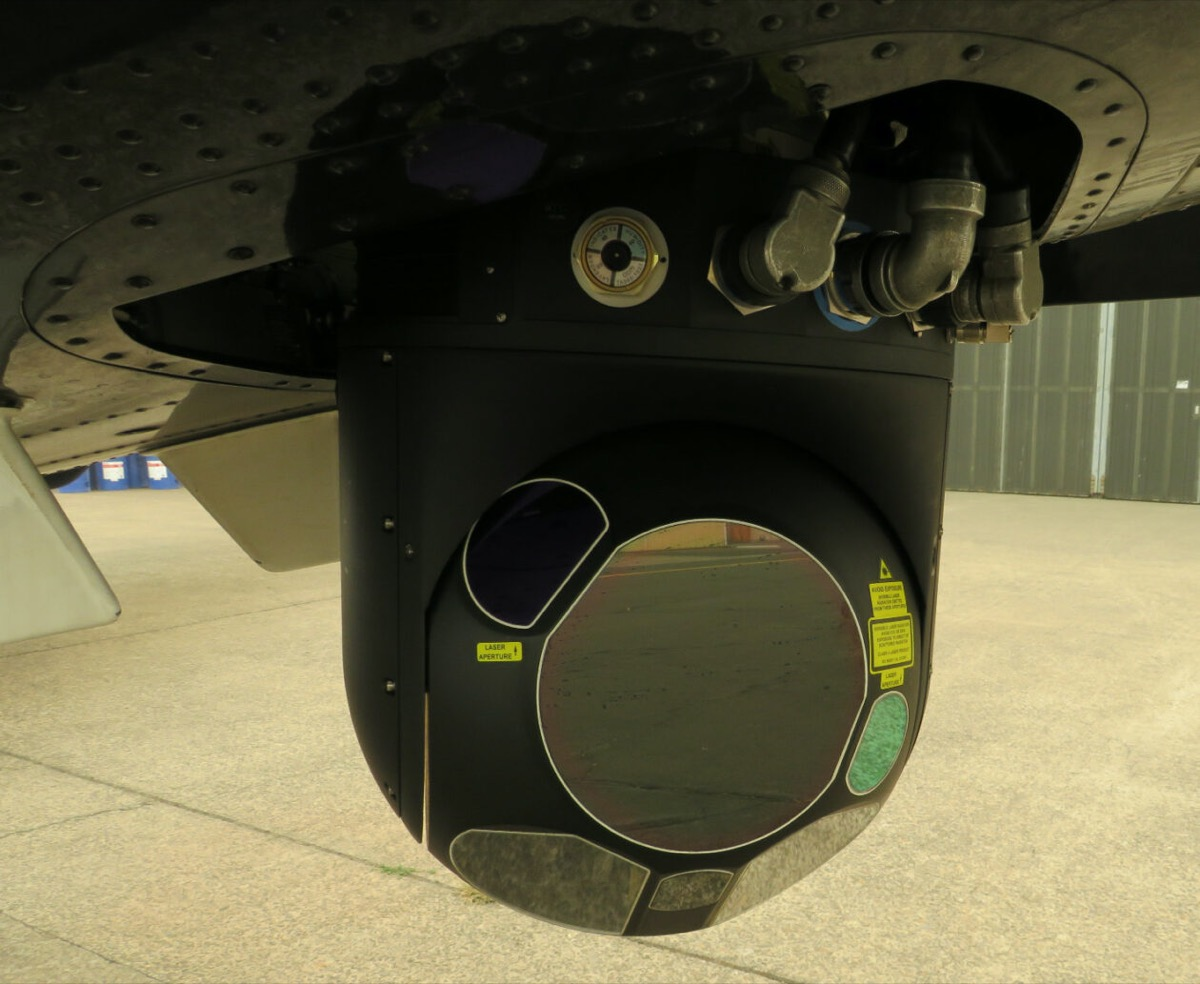 a close up of a black camera attached to a plane wing