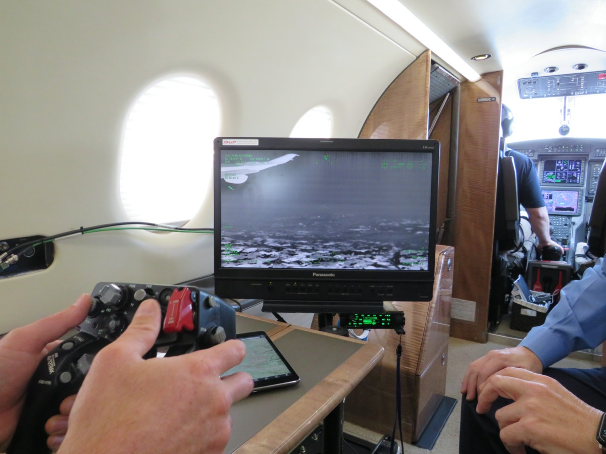 a person uses a video game-like controller to maneuver a camera's view on a computer screen. the person is doing it from inside the cabin of a plane