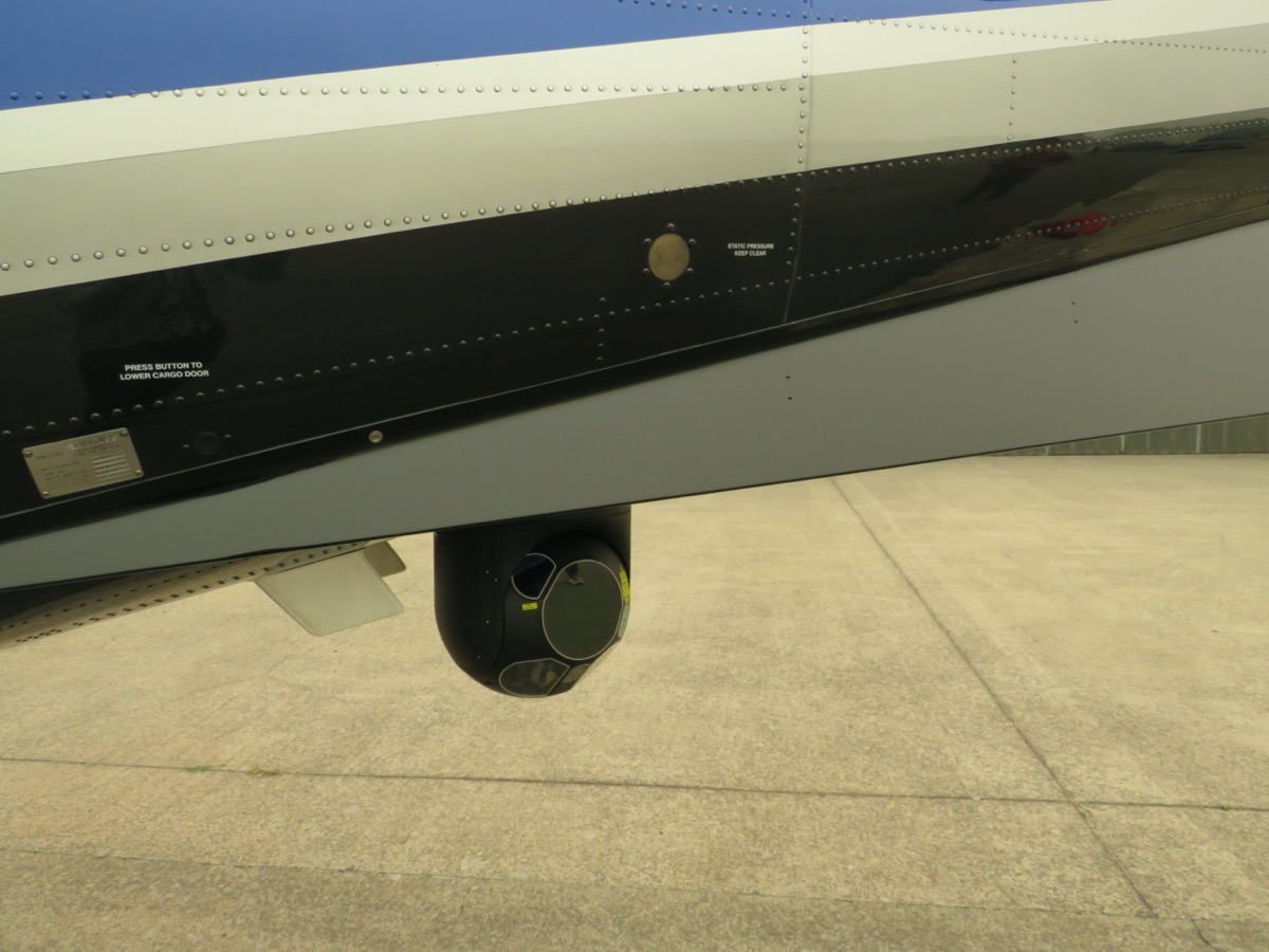 a small black camera attached to the wing of a plane