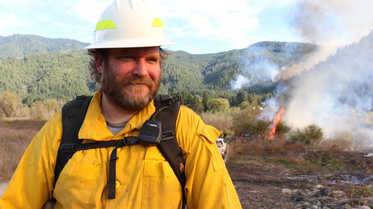 an indigenous man in a yellow safety jacket and hard hat with small fires burning behind him