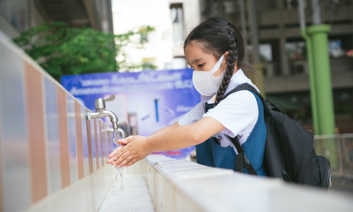 an asian student washing hands at an outdoor wash basin in a school wearing a face mask