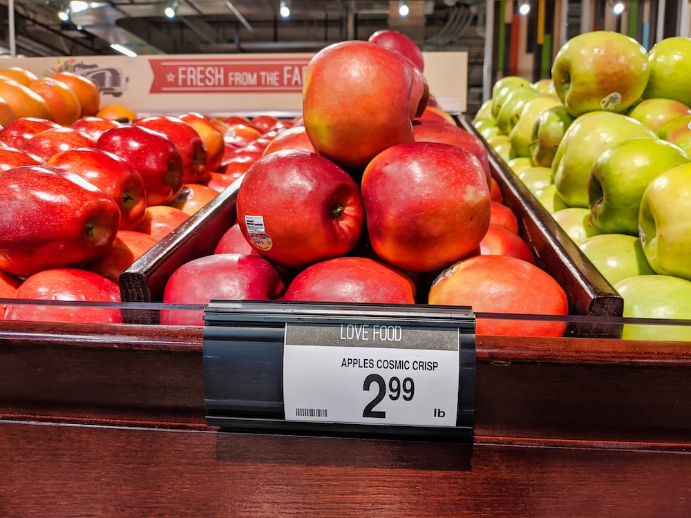 shiny reddish-pink apples stacked in a pyramid in a grocery store with a tag for price of $2.99