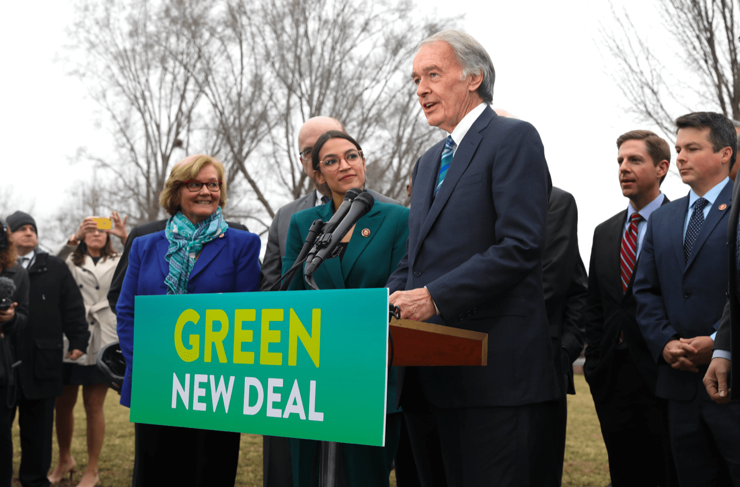 """ed markey stands at a podium that says """"green new deal"""" flanked by people to his right, including alexadria ocasio-cortez"""