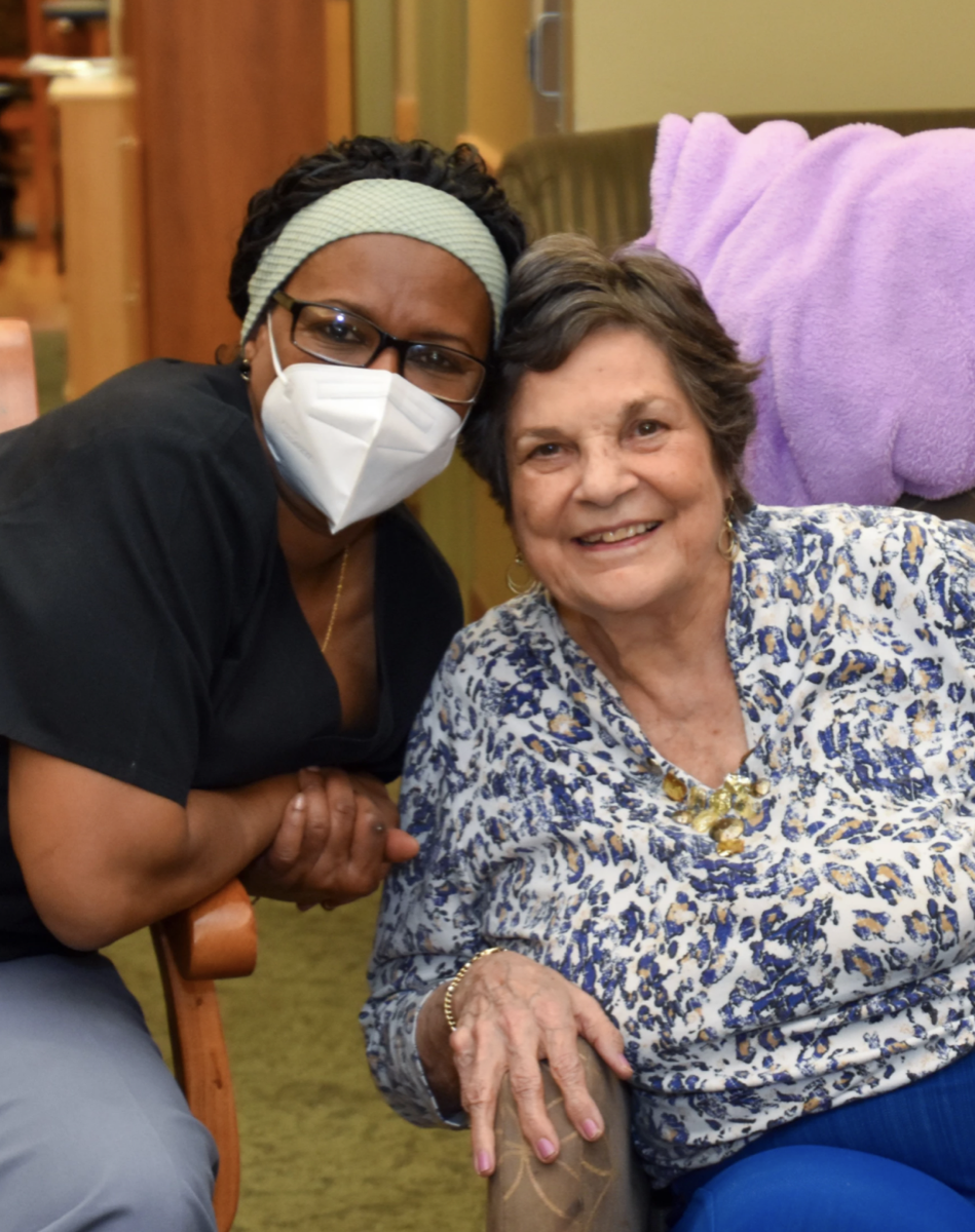 a nurse in a mask crouches next to an older lady in a nursing home