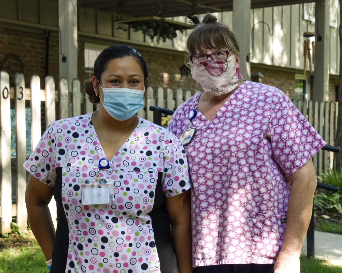 two nurses in masks standing outside a nursing home