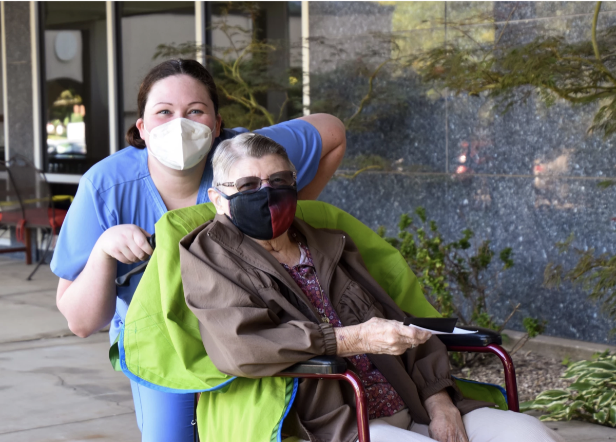 a nursing aid with a mask on pushing an older woman in a mask in a wheelchair.