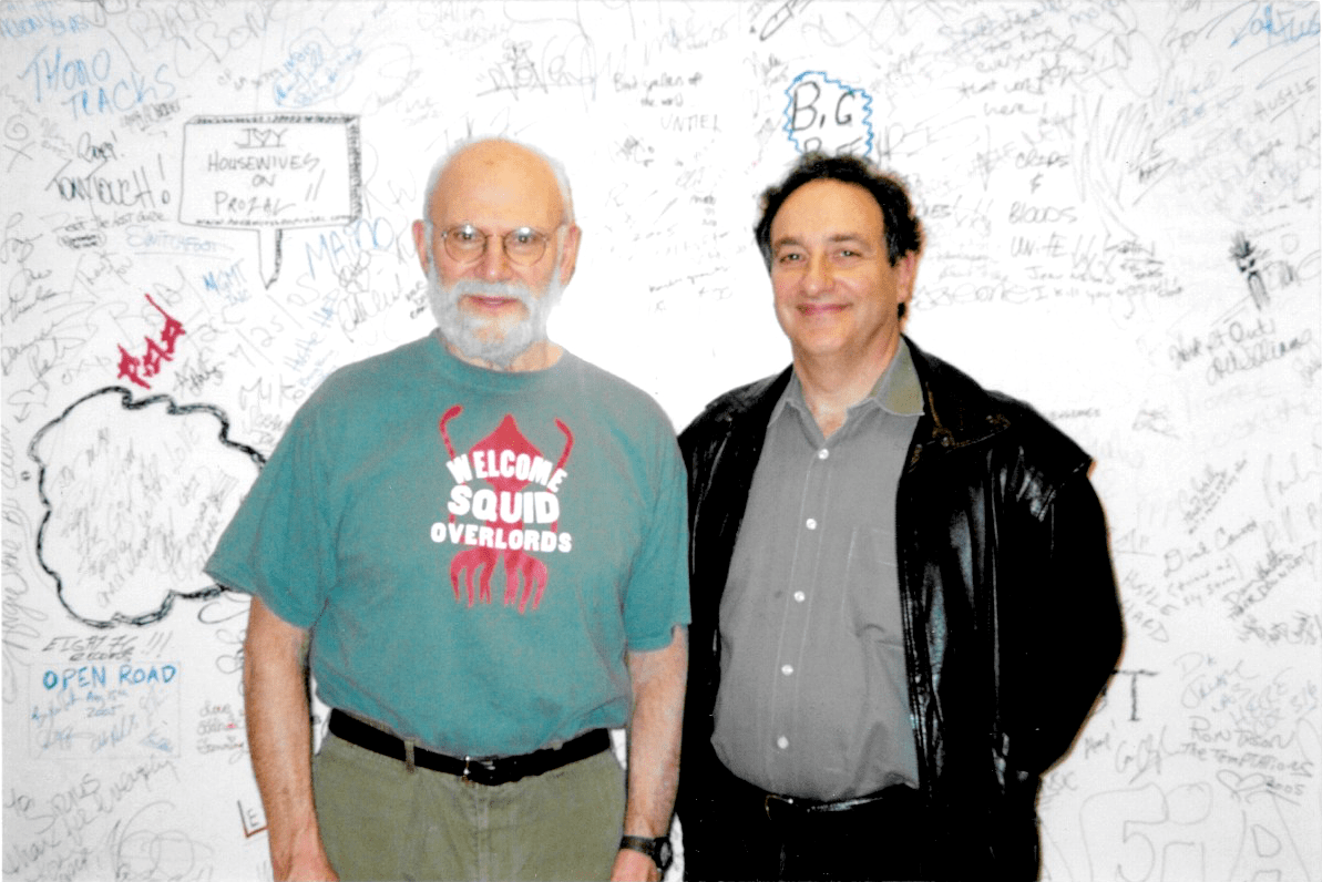 oliver sacks and ira flatow smiling at the camera in front of a wall filled with handwriting