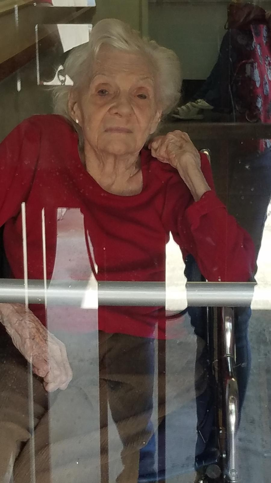 an image of an older woman in a red sweater - seen through a window