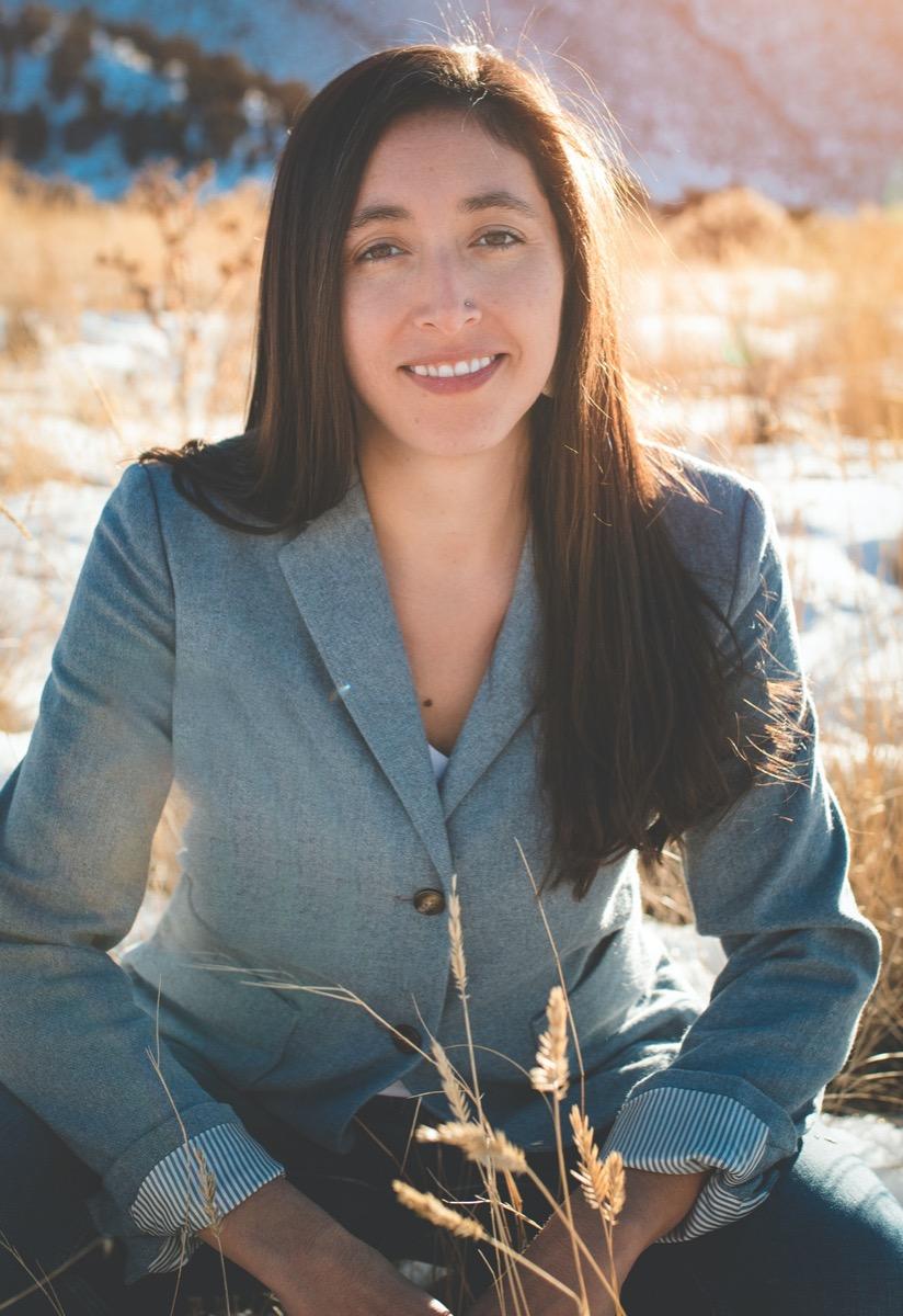 a profile photo of a women in a blazer sitting in a field