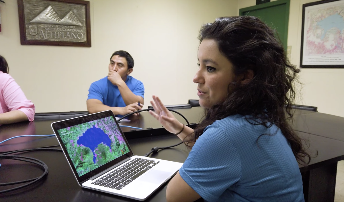 a woman sits in front of a laptop with a satellite image of a lake and she speaks to a table of fellow scientists