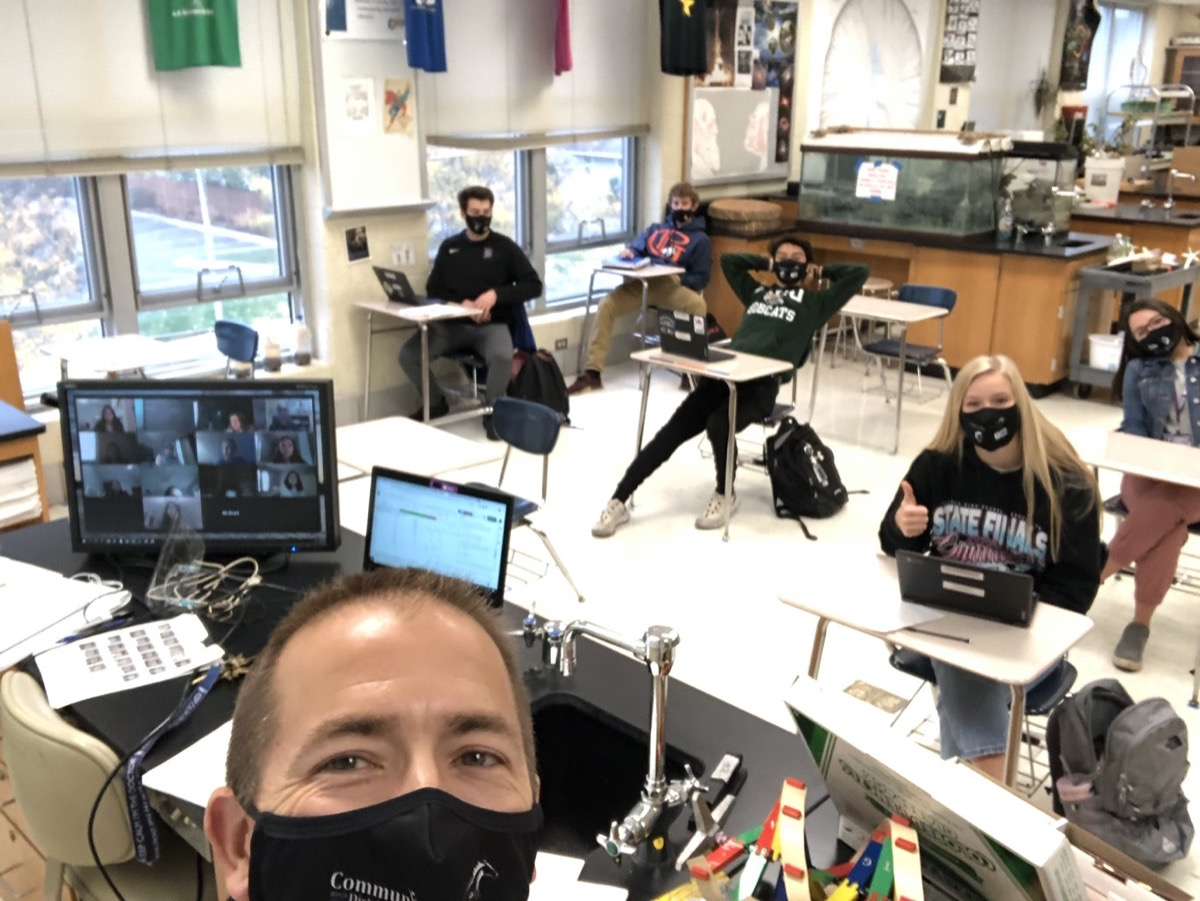 a male teacher with a black face mask takes a selfie of his classroom with remote students on a computer screen, and other students sitting six feet apart with masks at desks