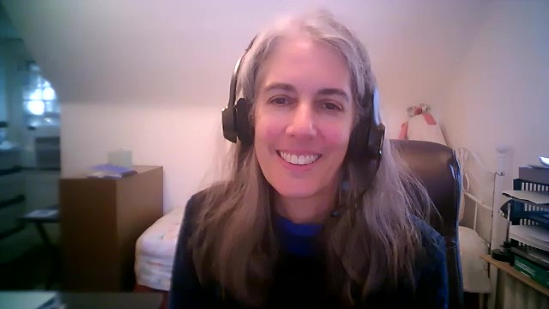 a screenshot from a video chat of a White woman smiling wearing a headset