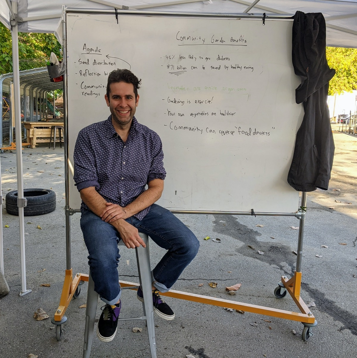 a man sitting on a stool outside in front of a white board. it's an outdoor classroom!