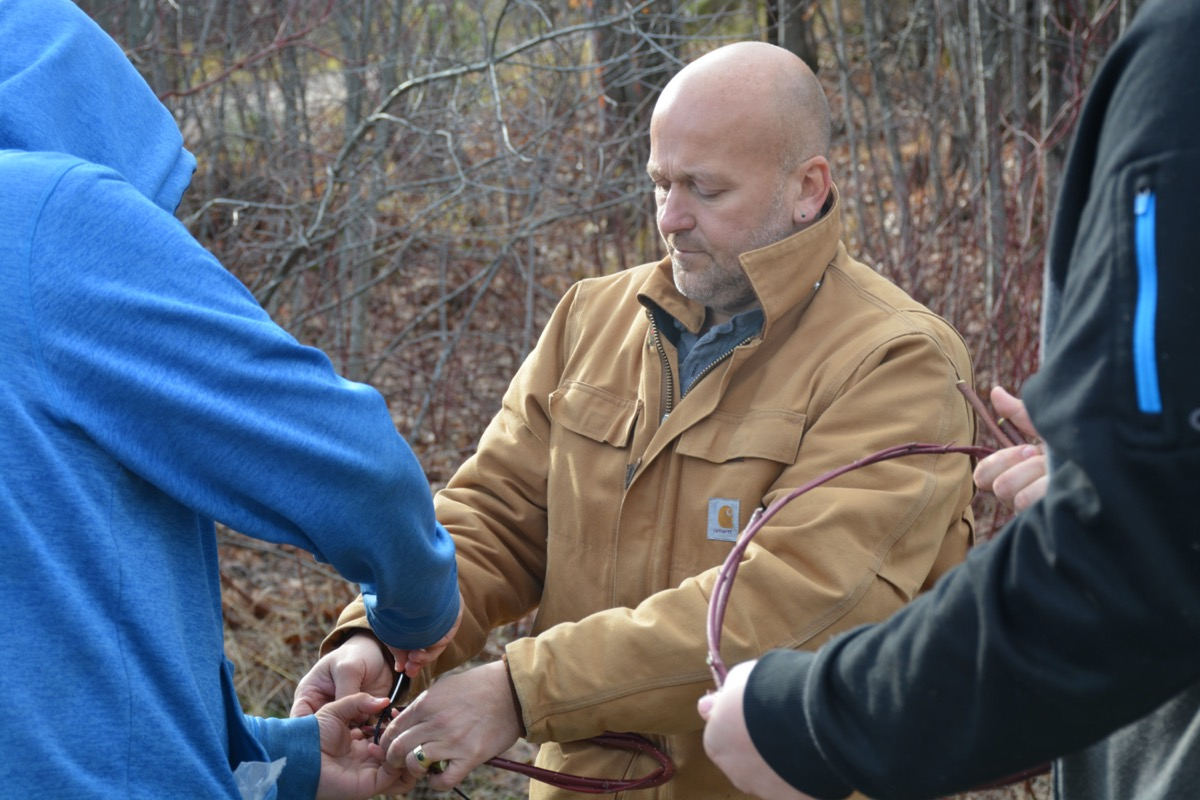a bald man with a brown coat working with students outside