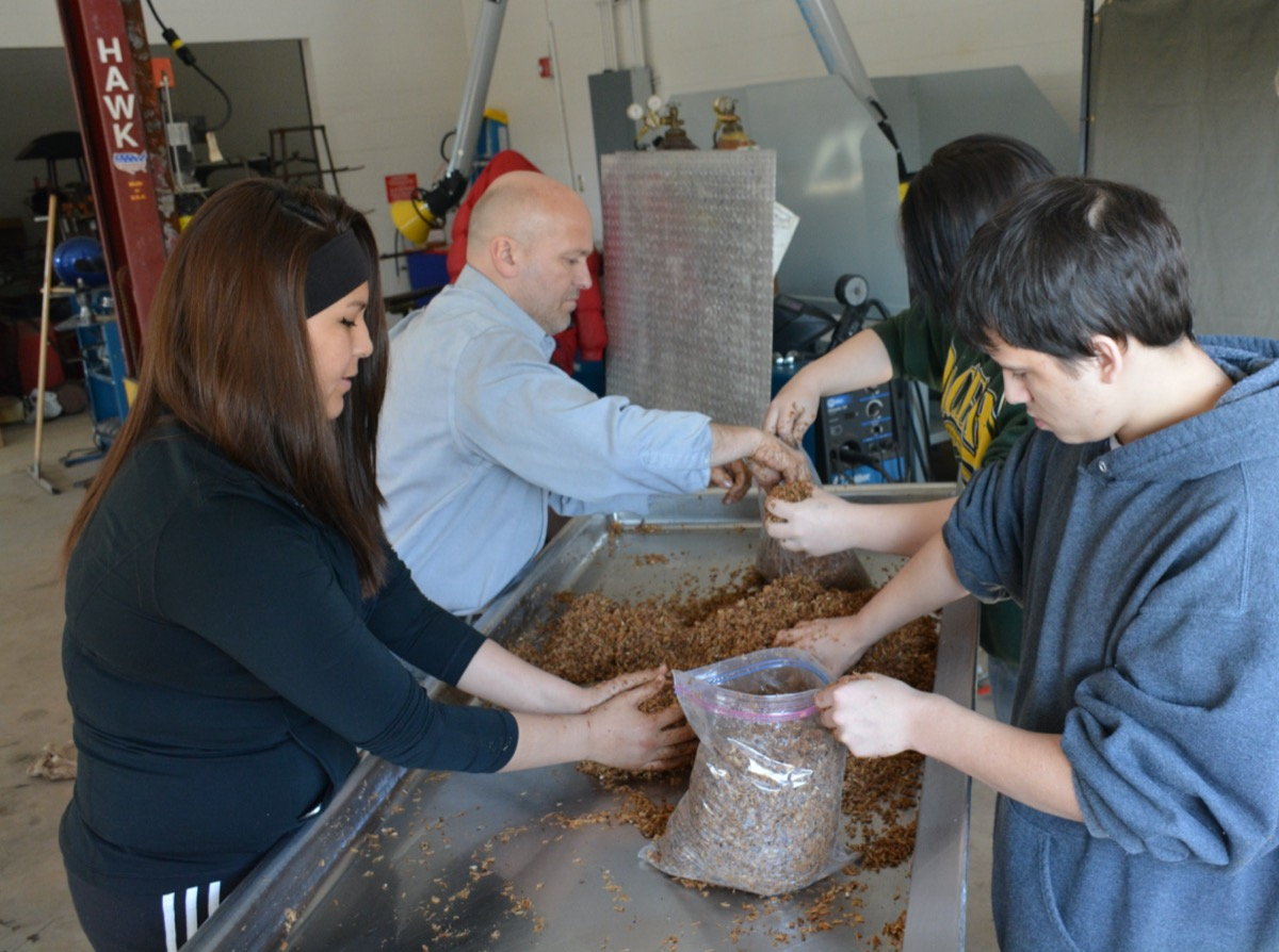 four people putting brown material into bags.