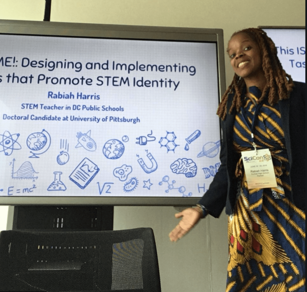"""a black woman stands next to a board that's slightly cut off in the photo. it reads """"designing and implementing... that promotes stem identity."""""""