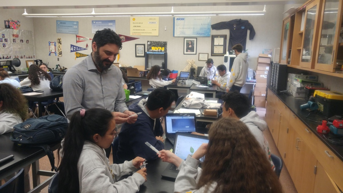 a teacher stops by a group of students in his classroom working on computers