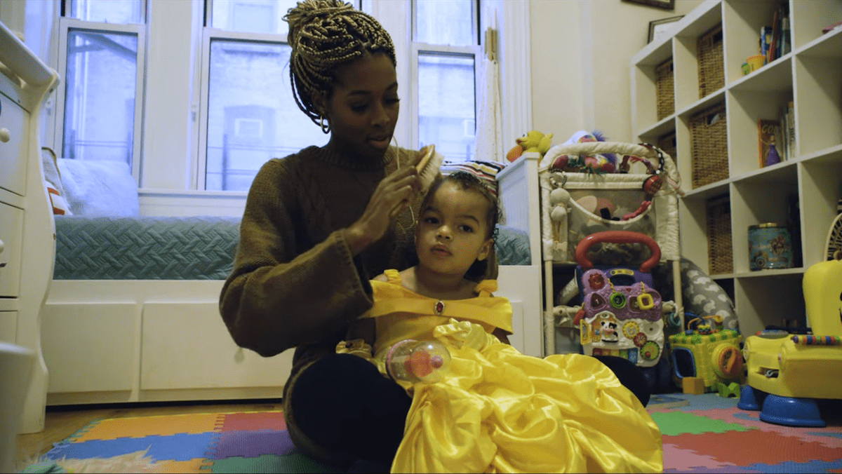 a black woman and combs her daughter's hair