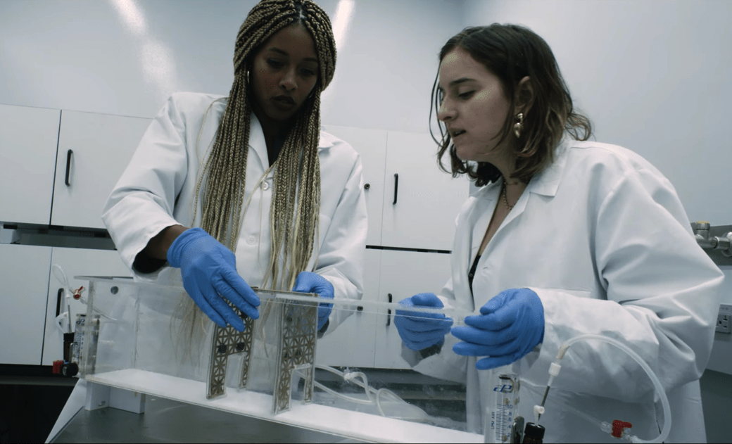 a black woman scientist and a female research assistant with lab coats and gloves on assemble a clear observation box