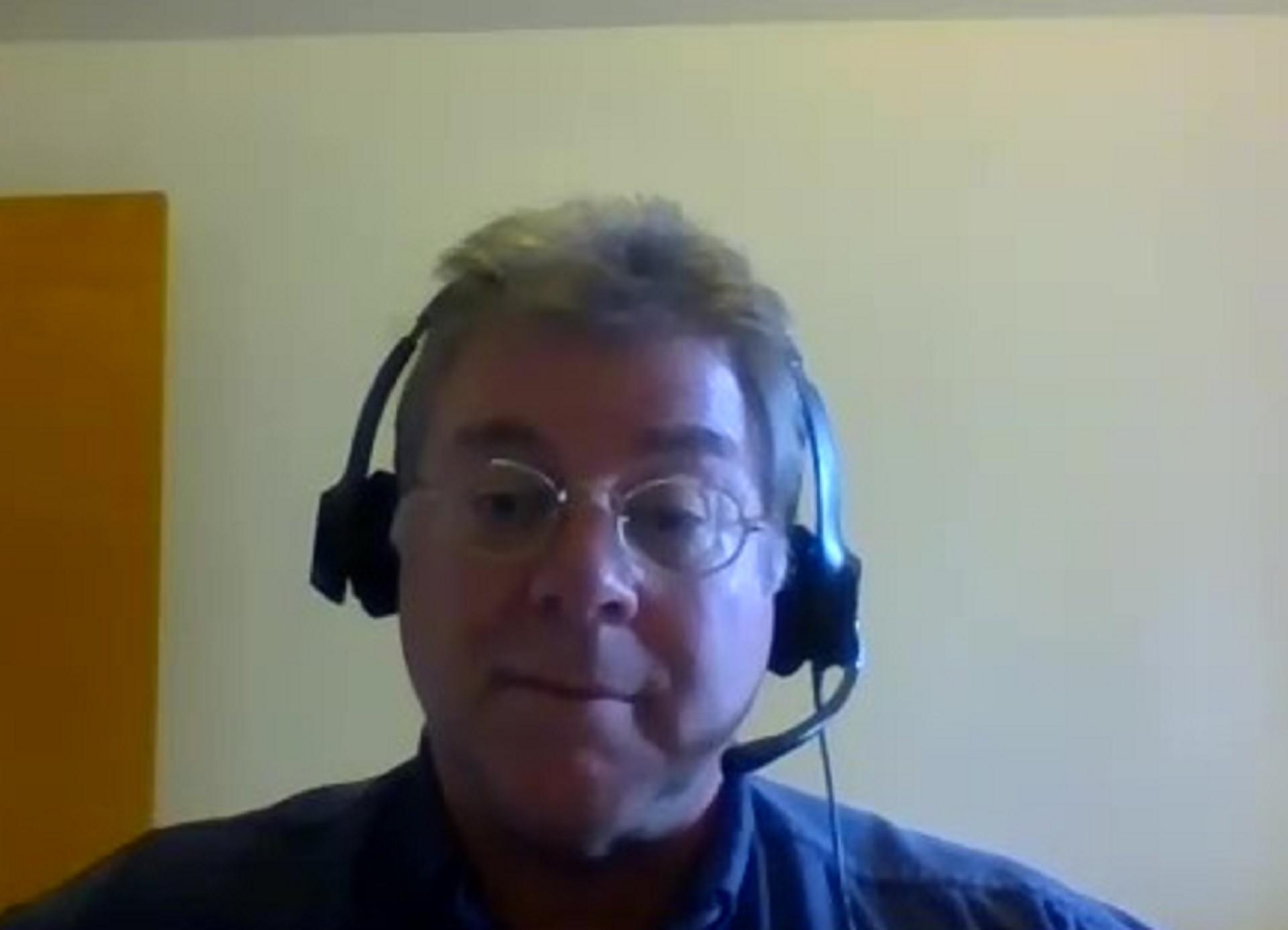 a video chat screenshot of an Asian man wearing a headset