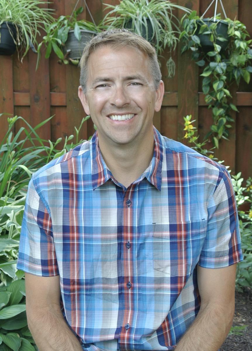 a profile photo of a man in a plaid shirt
