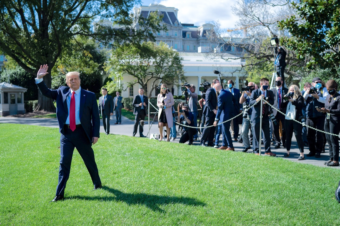 trump walking on a lawn, waving at people and press
