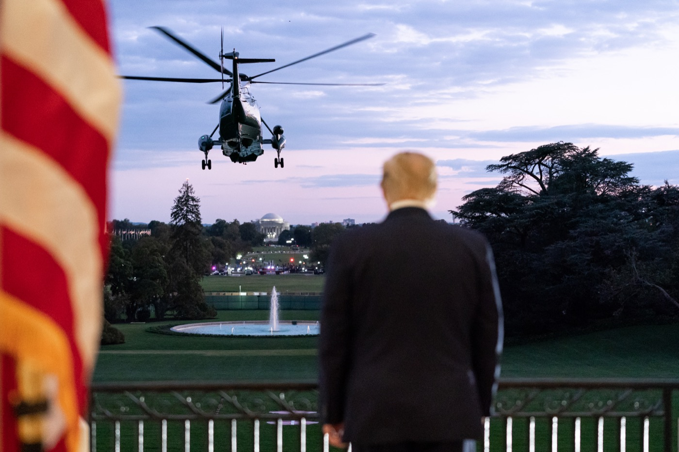 trump from behind on the balcony of the white house as he watches a helicopter flies away