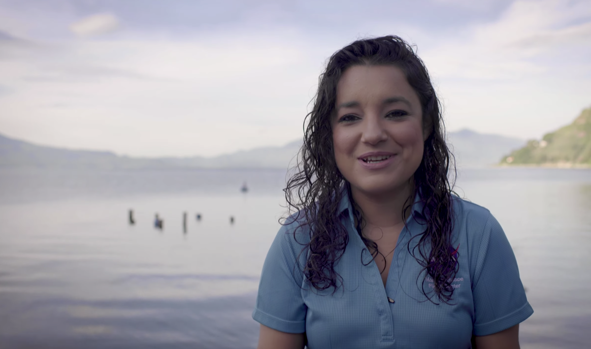 a woman with wavy hair and wearing a blue polo shirt sits in front of a beautiful lake. she's smiling