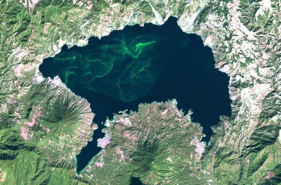 a satellite image of a lake with small waves of green algae