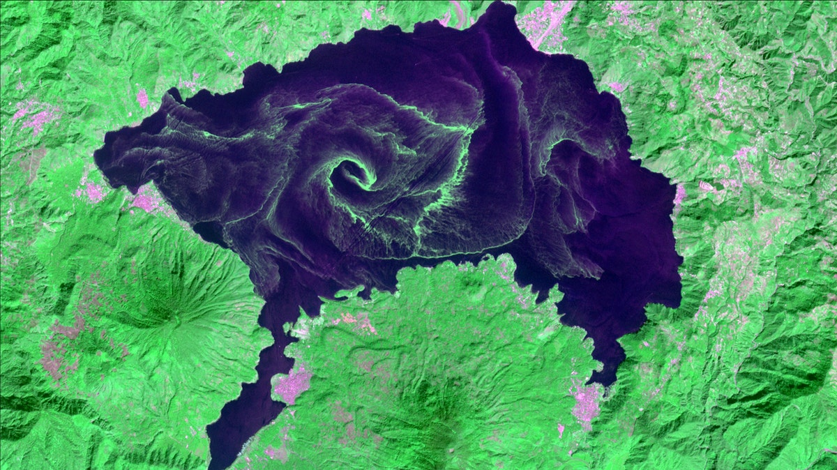 a satellite image of a lake that has large green swirls of algae in it