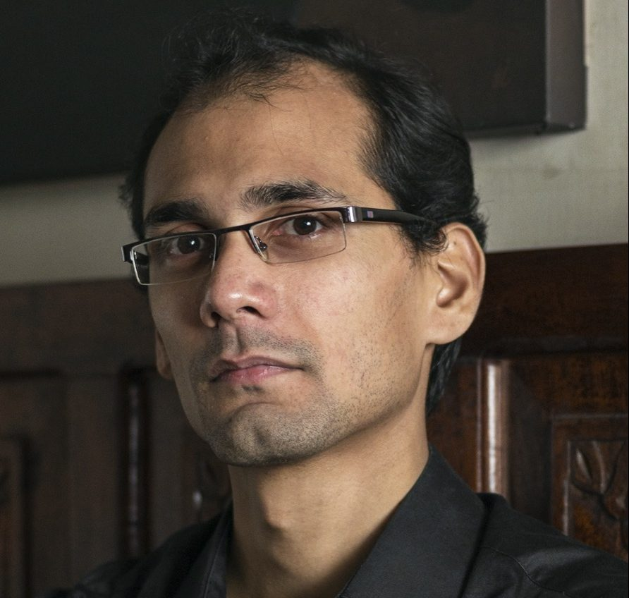 a portrait of a indian man with glasses in a black shirt