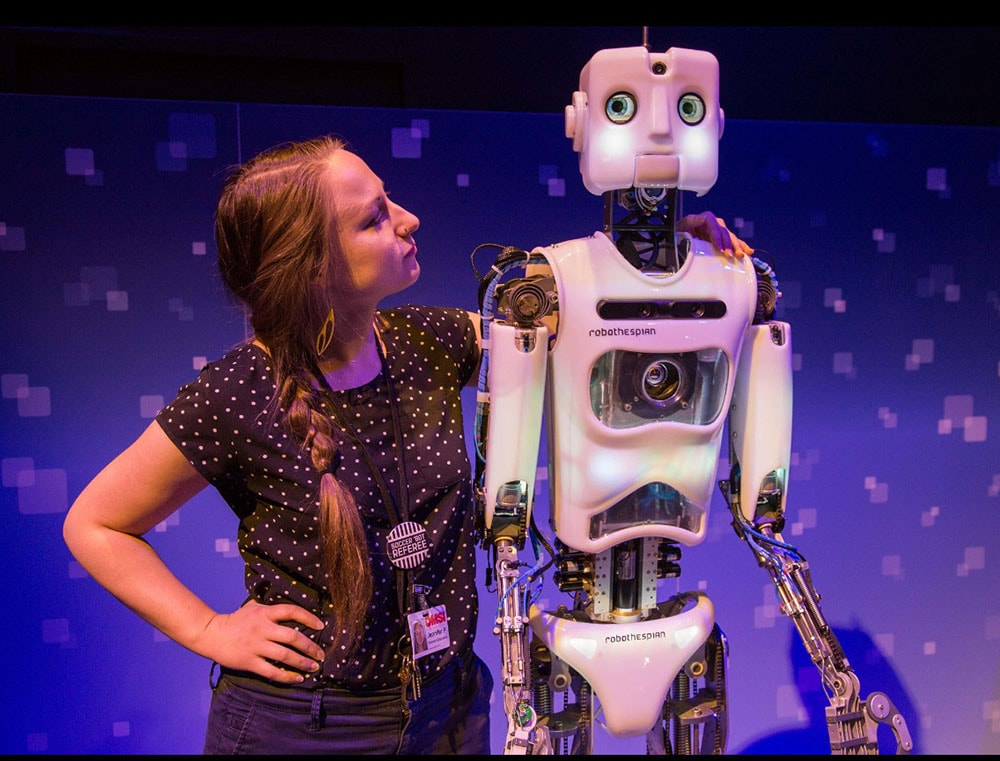 a White woman standing next to a tall humanoid robot