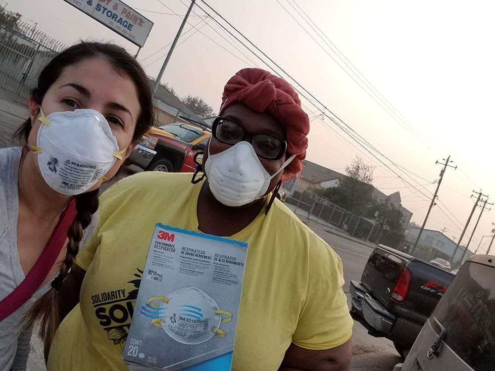 a Latino woman and a Black woman wearing face masks pose for the camera with smoke in the background